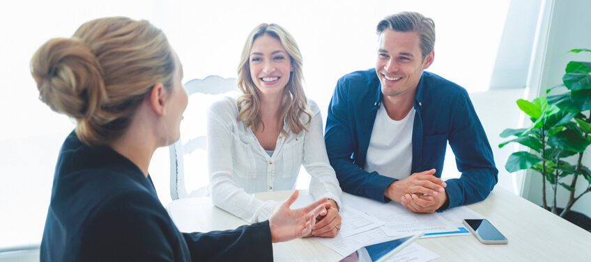 A real estate agent with a couple discussing the terms of the real estate documents