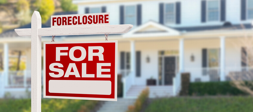 A foreclosure homes for sale sign in front of a single-family home