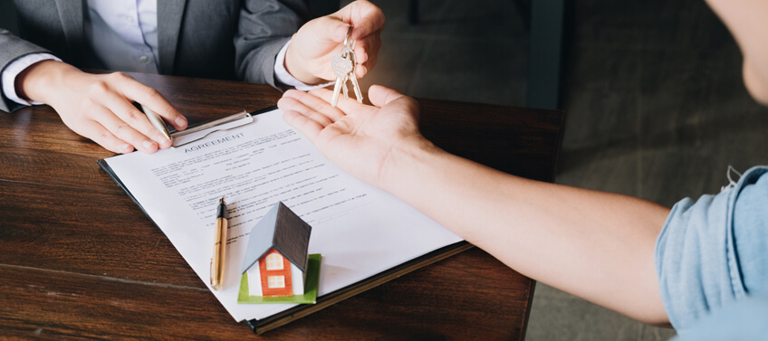 A real estate agent giving the house keys to the new homeowner after signing the closing agreement