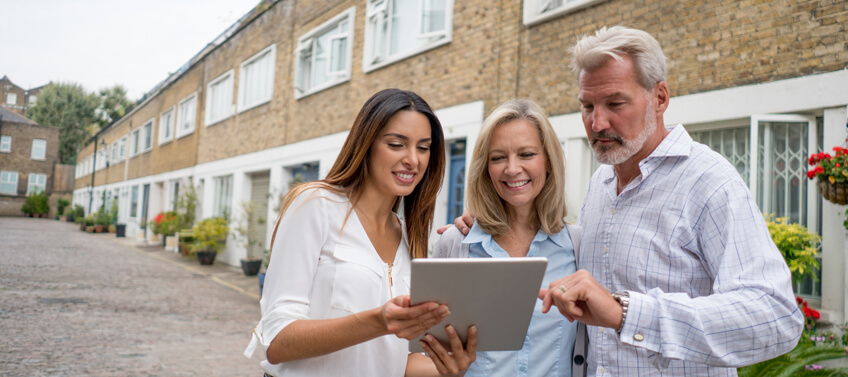 A realtor showing a real estate contract through her tablet to an old couple